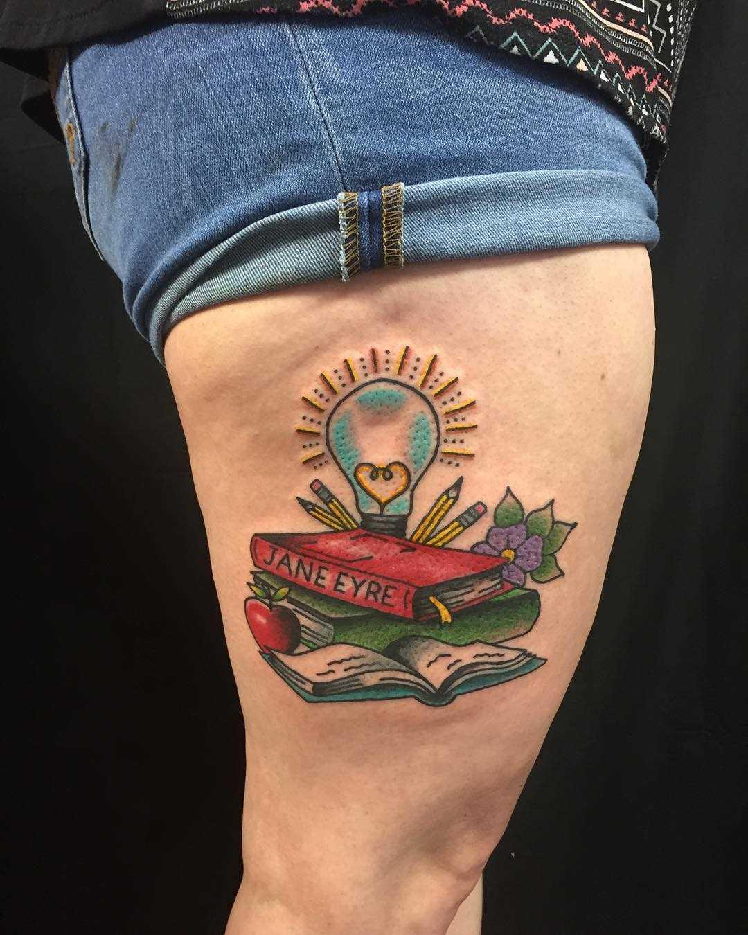 Tatuagem de livros com uma lâmpada no quadril da menina