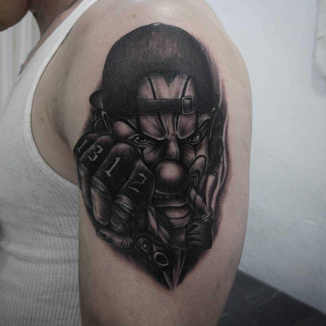 Tatuagem de palhaço no ombro do cara
