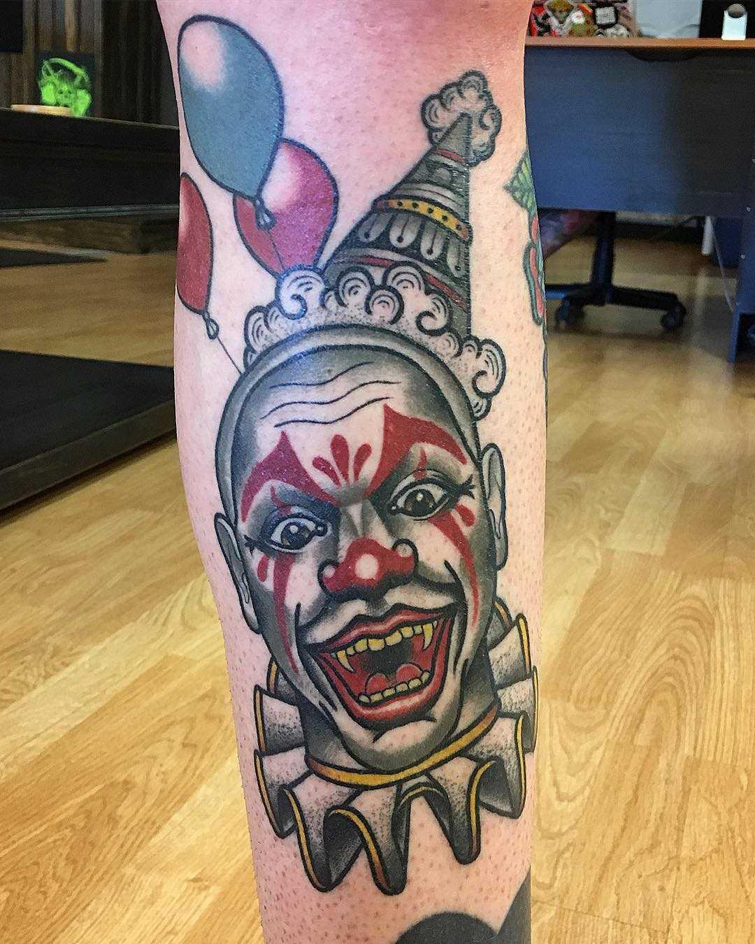 Tatuagem de palhaço sobre a perna de um cara