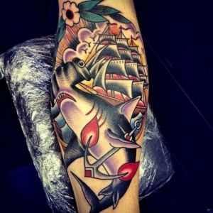 Tatuagem de peixe-martelo e o veículo sobre a perna de um cara