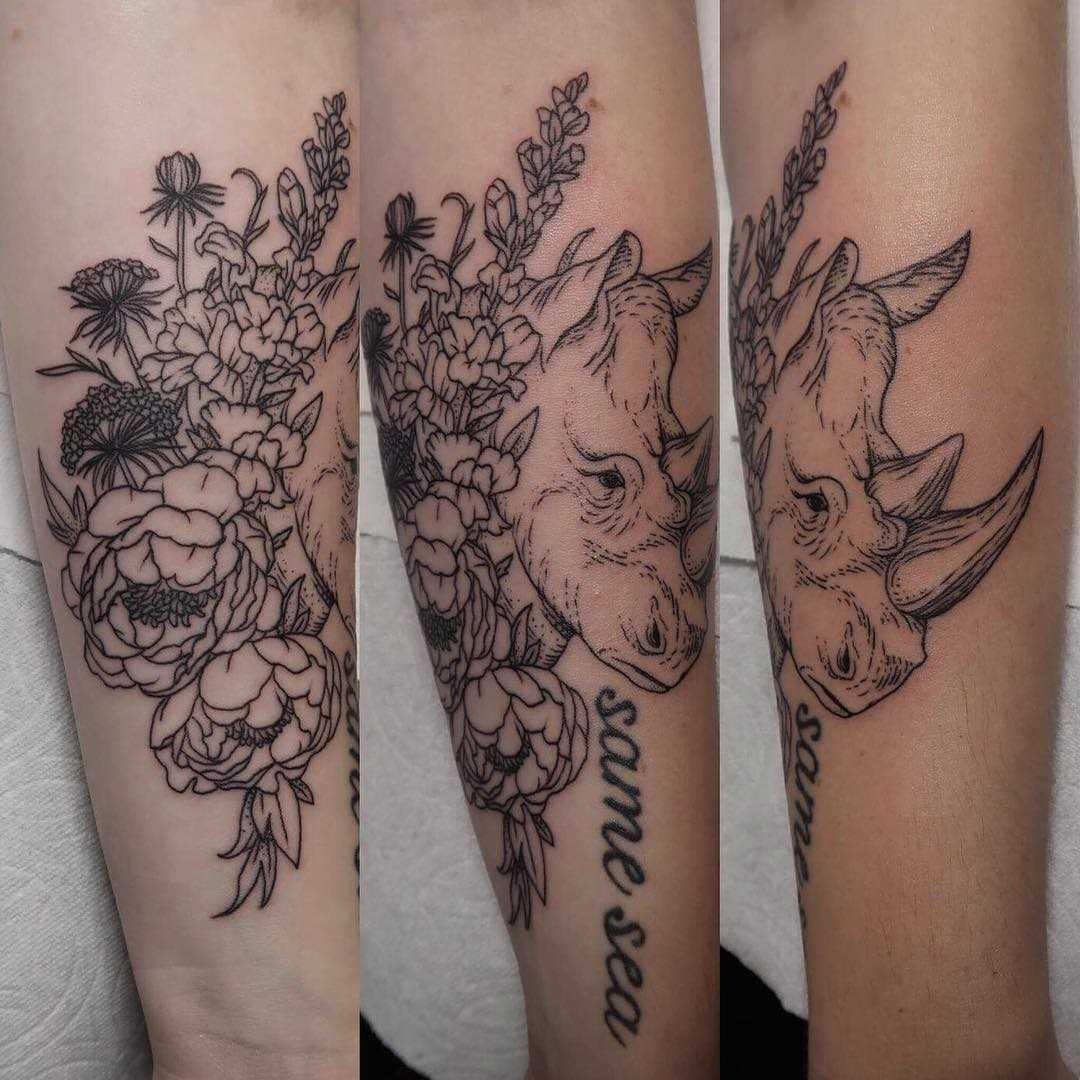 Tatuagem de rinoceronte com flores no antebraço da menina