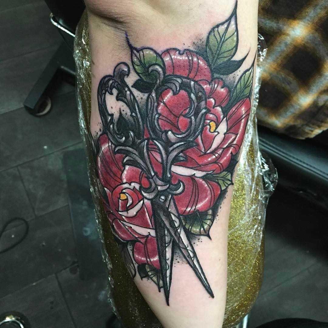 Tatuagem de tesoura com as rosas no antebraço da menina