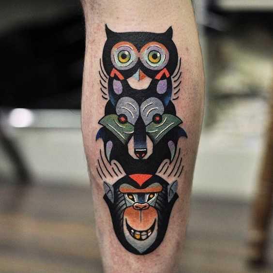 Tatuagem de totem de corujas lobo e macacos sobre a perna de um cara