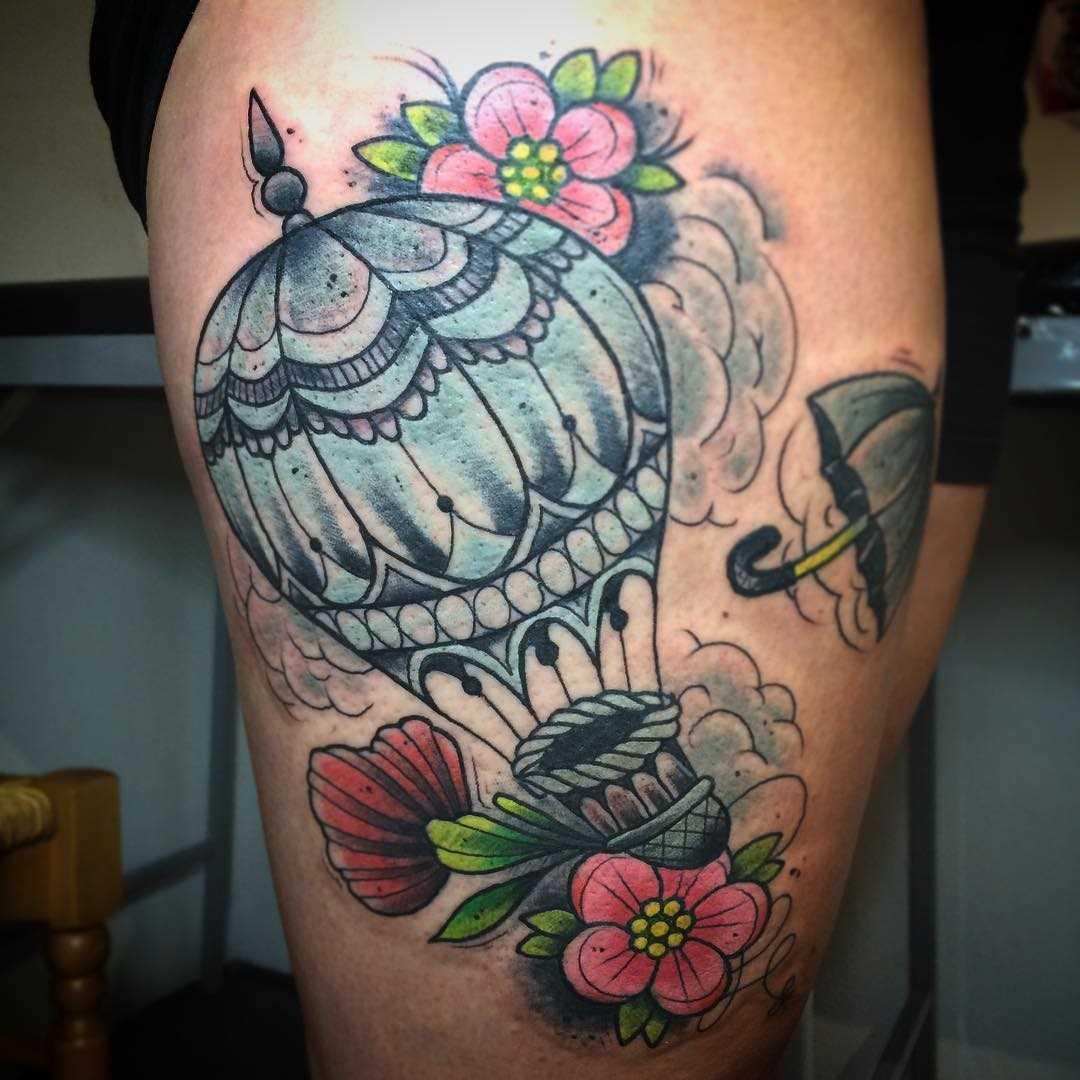 Tatuagem de um balão com as cores no quadril da mulher