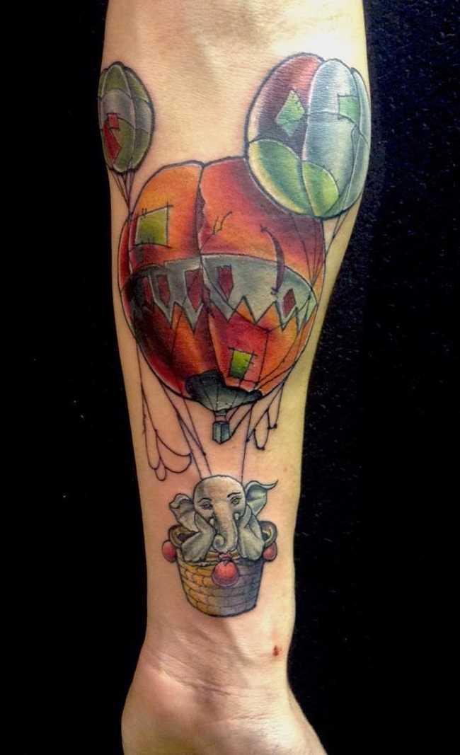 Tatuagem de um balão de ar com um elefante no antebraço cara