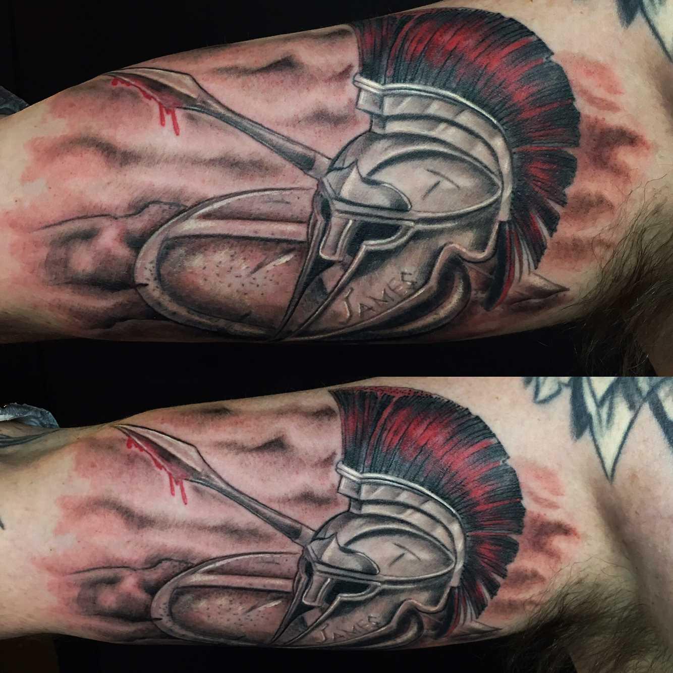 Tatuagem de um capacete espartano com um escudo na mão de homens
