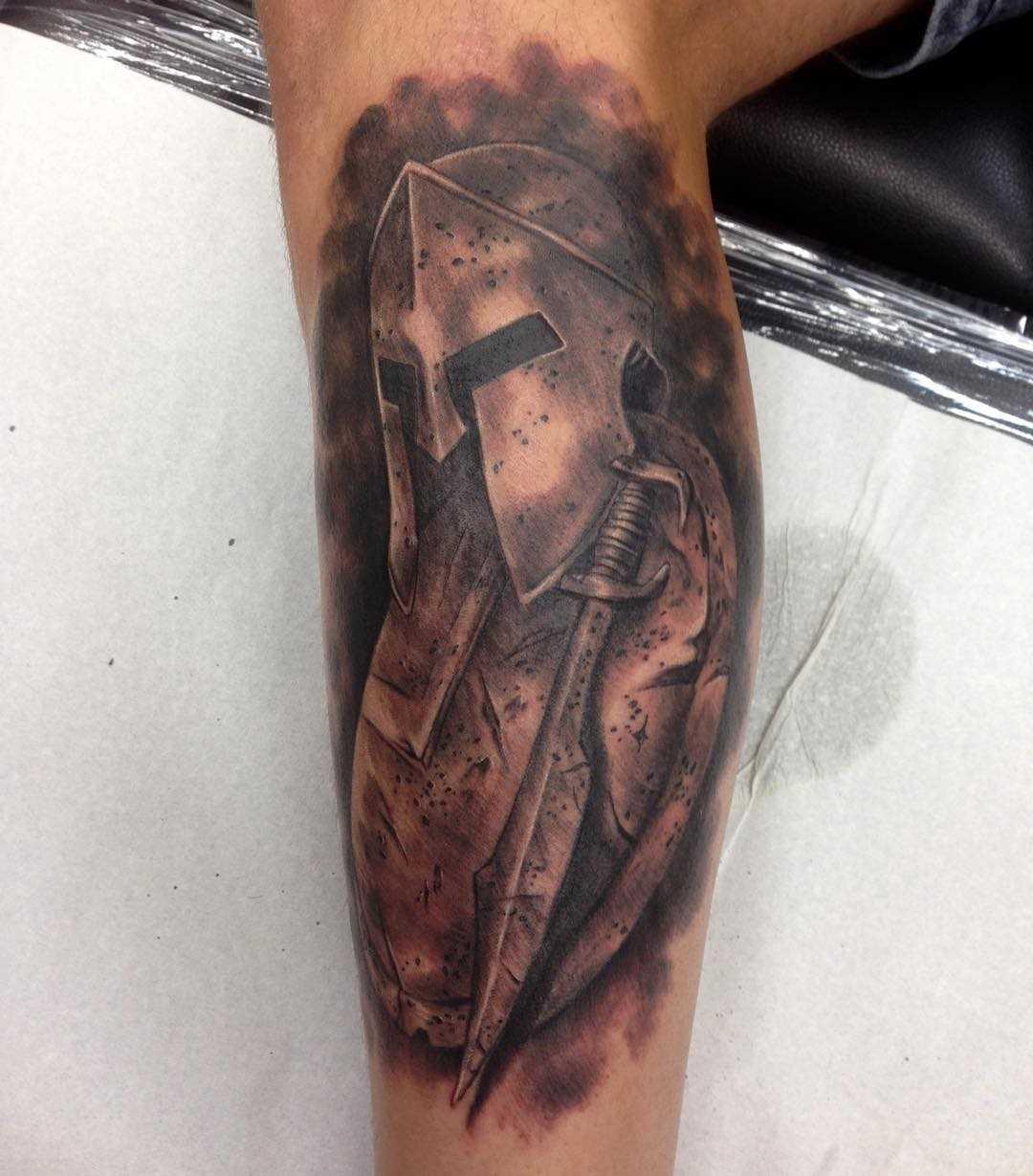 Tatuagem de um capacete espartano com um escudo sobre a perna de um cara