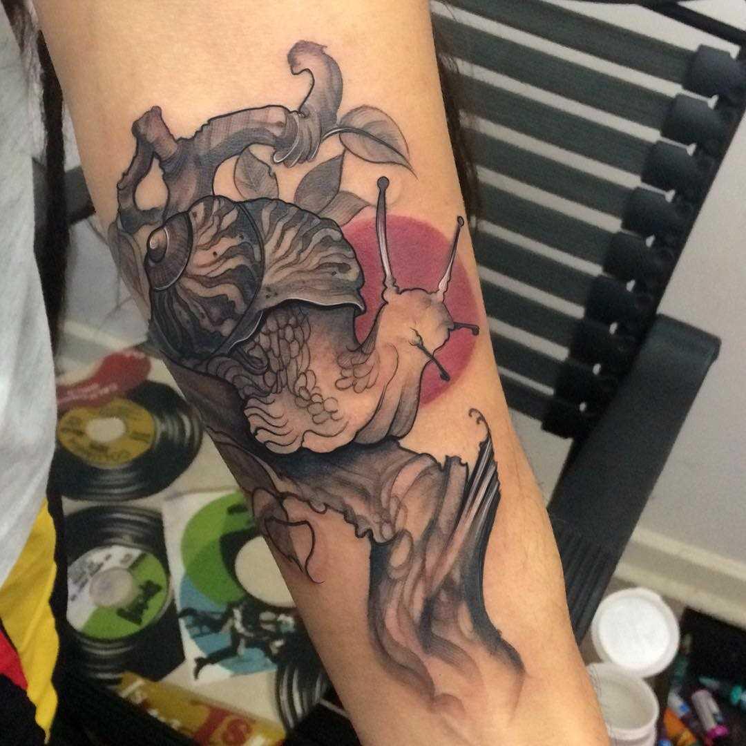 Tatuagem de um caracol no antebraço da menina