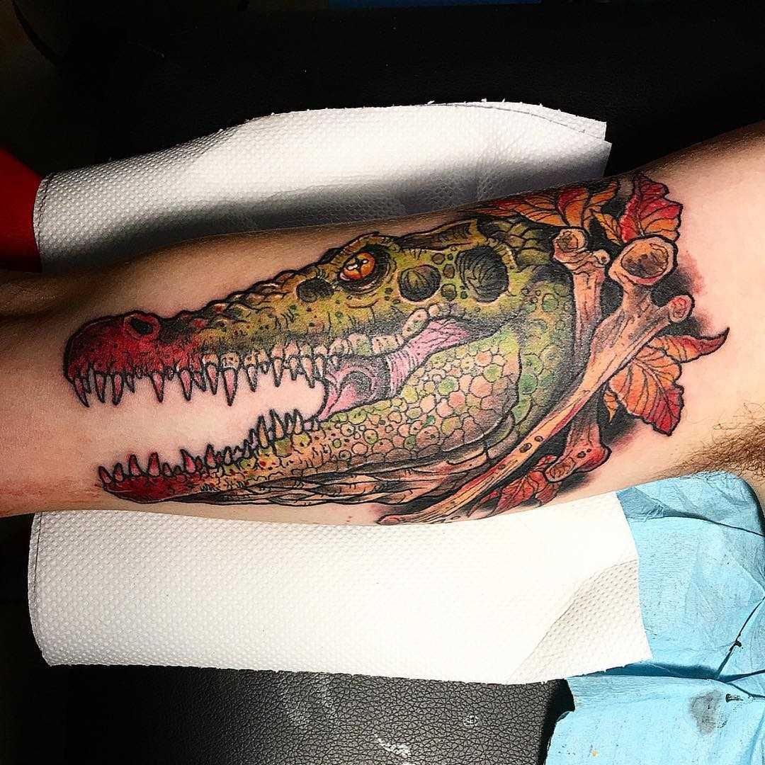 Tatuagem de um crocodilo na mão de um cara