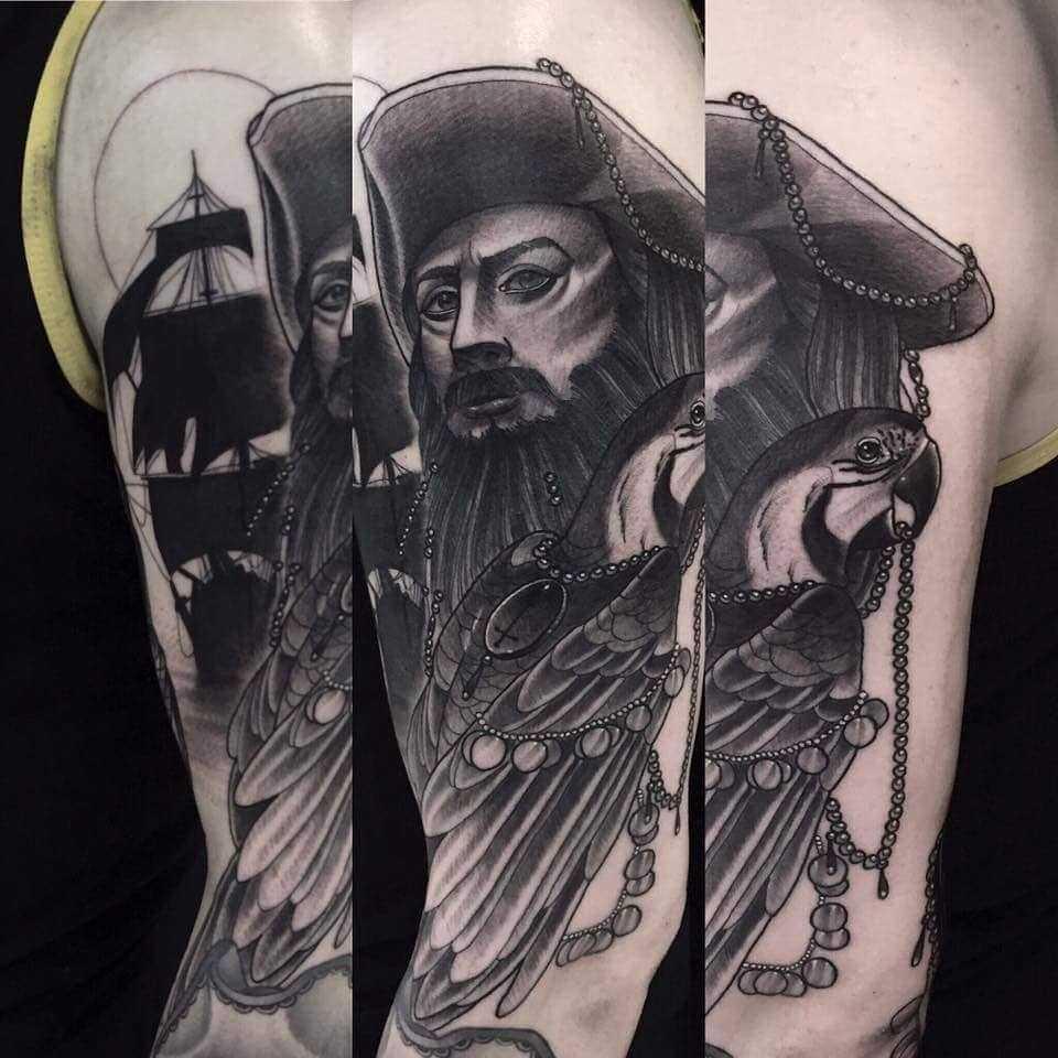 Tatuagem de um pirata com papagaio no ombro do cara