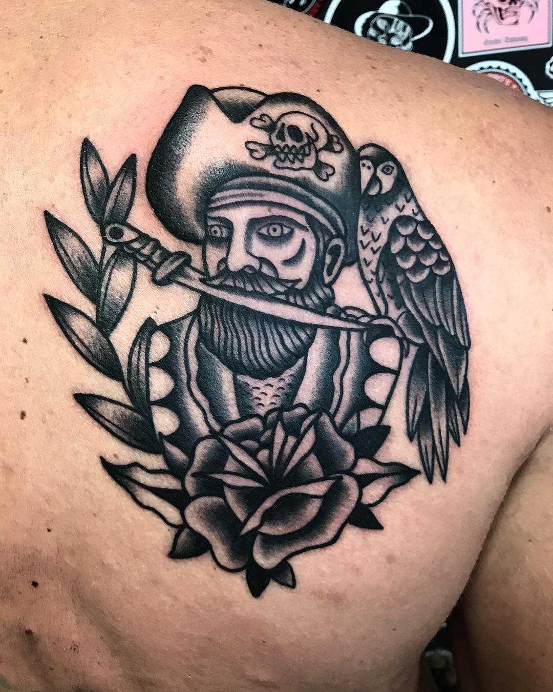 Tatuagem de um pirata com uma rosa na lâmina cara