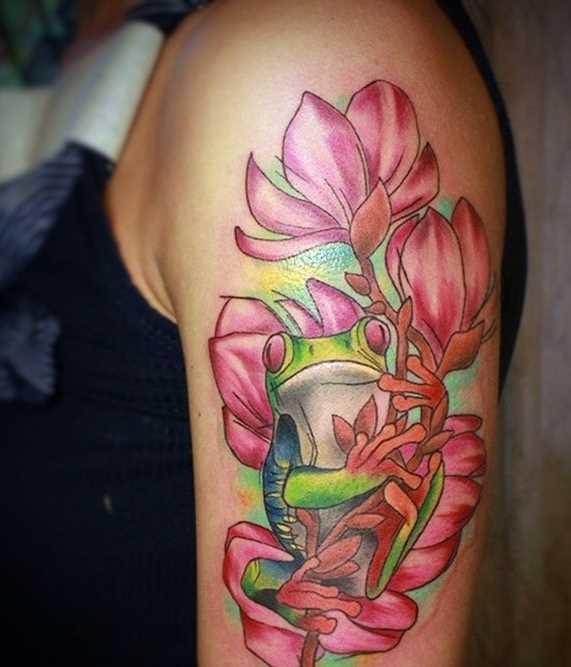 Tatuagem de um sapo com flores no ombro da menina