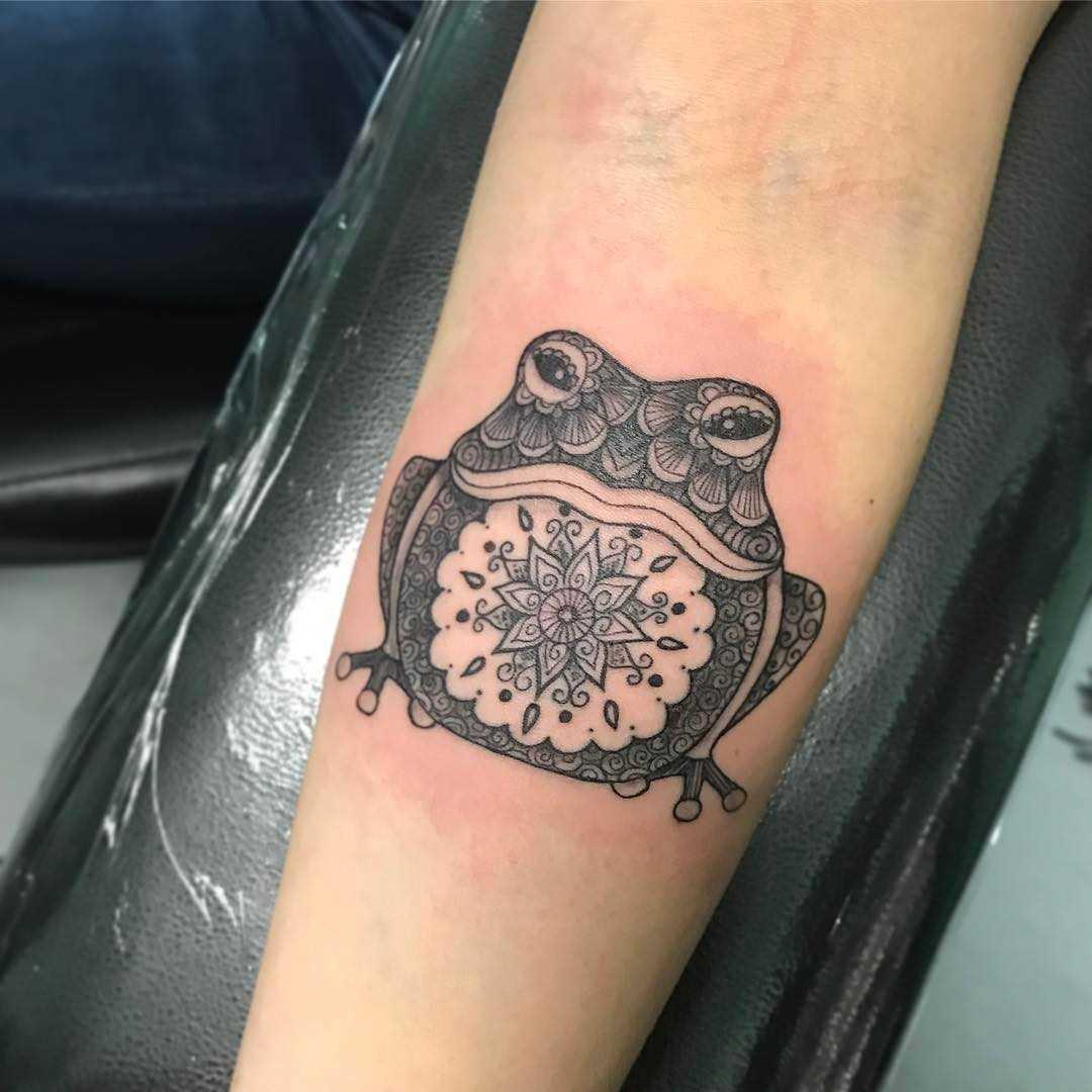 Tatuagem de um sapo no antebraço da menina