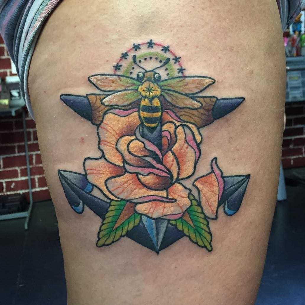 Tatuagem de uma abelha com uma flor no quadril da mulher