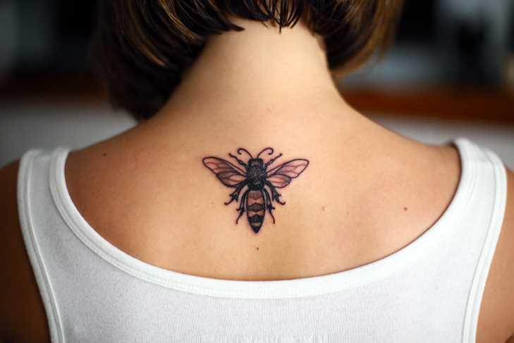 Tatuagem de uma abelha na coluna da menina
