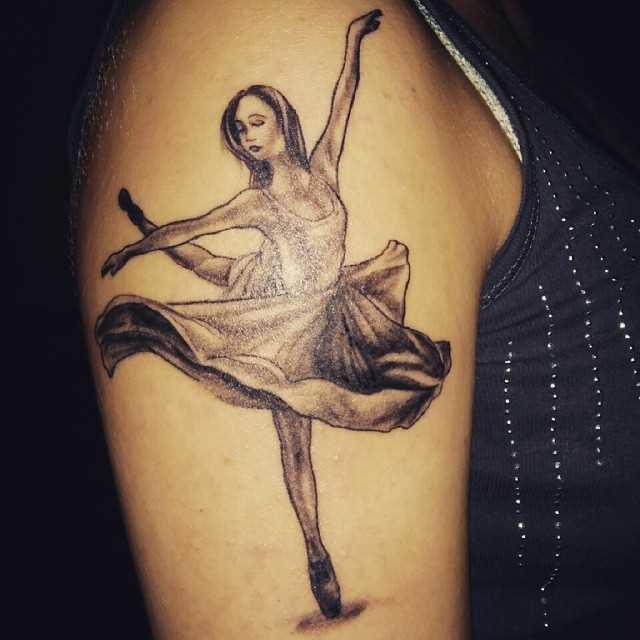 Tatuagem de uma bailarina no ombro da mulher