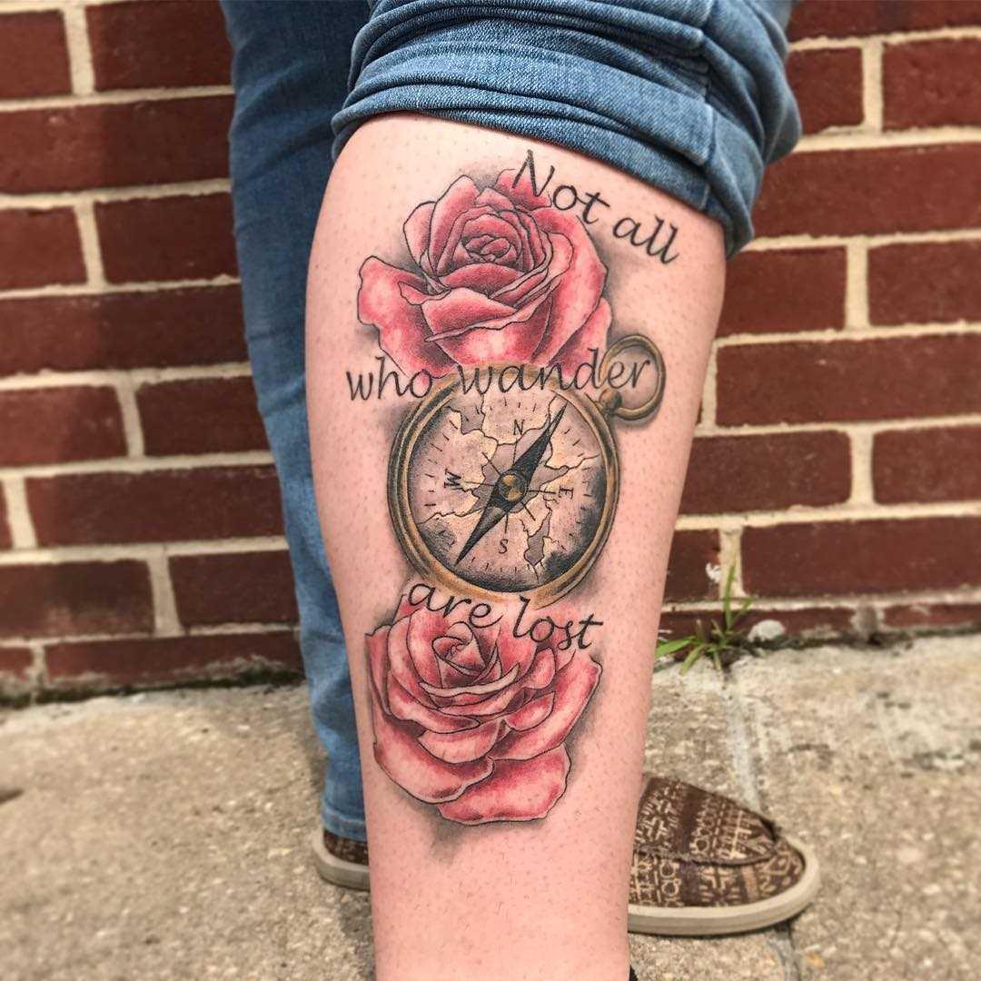 Tatuagem de uma bússola, com rosas sobre a perna da mulher