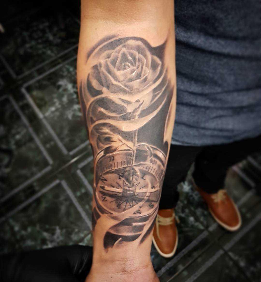Tatuagem de uma bússola, com uma rosa no antebraço cara