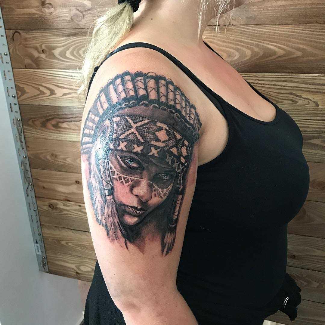 Tatuagem de uma menina indígena no ombro da mulher