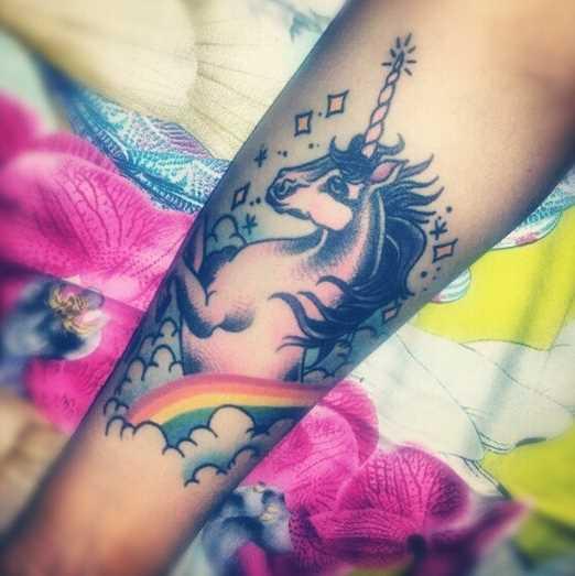 Tatuagem de uma menina no antebraço - o unicórnio e o arco-íris