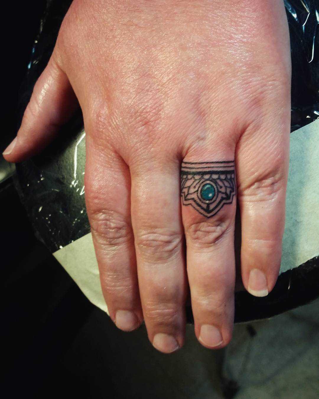 Tatuagem do anel no terceiro dedo da mulher