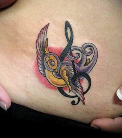 Tatuagem na barriga da menina - clave de sol e a andorinha
