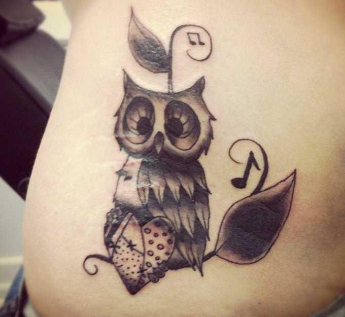 Tatuagem na barriga da menina de notas e coruja com o coração