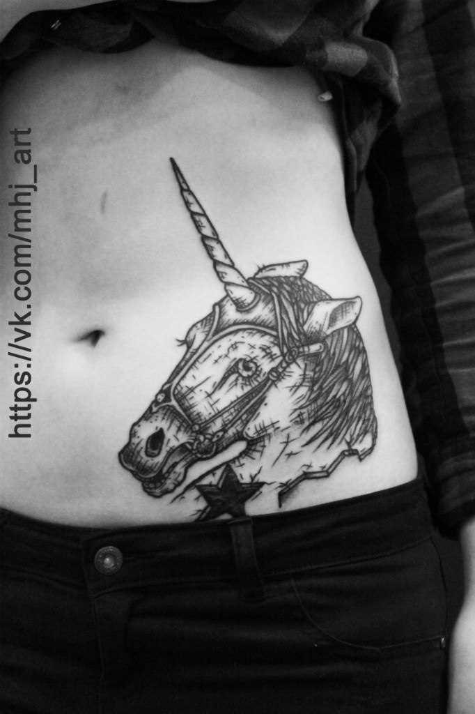 Tatuagem na barriga da menina - que é um unicórnio