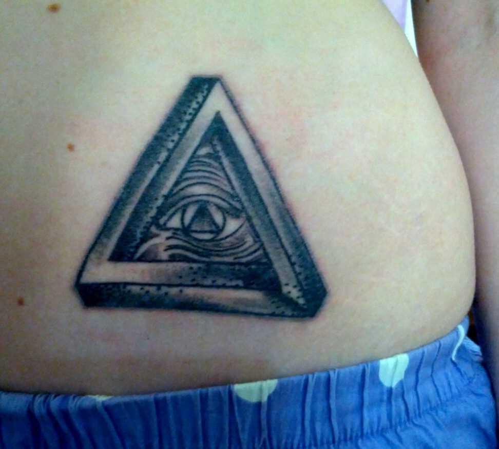 Tatuagem na barriga da menina - triângulo com o olho de