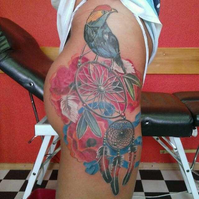 Tatuagem na coxa da menina - apanhador de sonhos e o pássaro