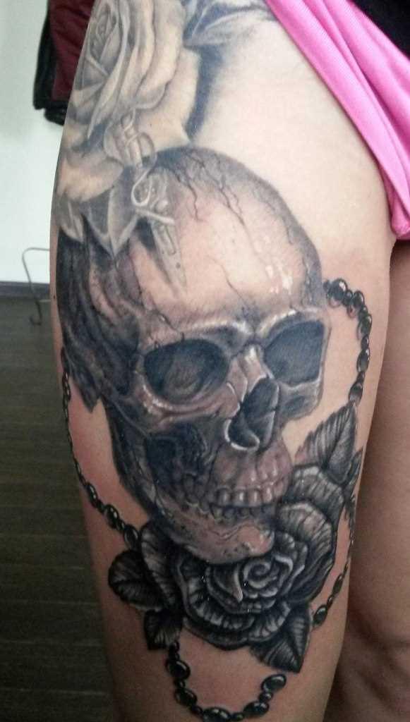 Tatuagem na coxa da menina de crânio e rosa