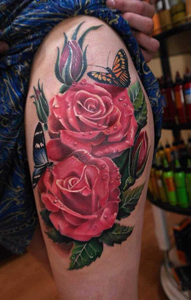 Tatuagem na coxa da menina - rosa e borboleta