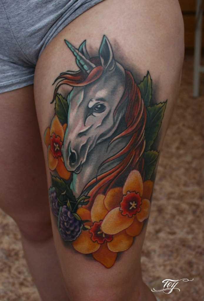 Tatuagem na coxa da menina - um unicórnio e flores