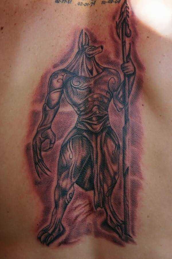 Tatuagem na espinha de um cara em forma de anubis