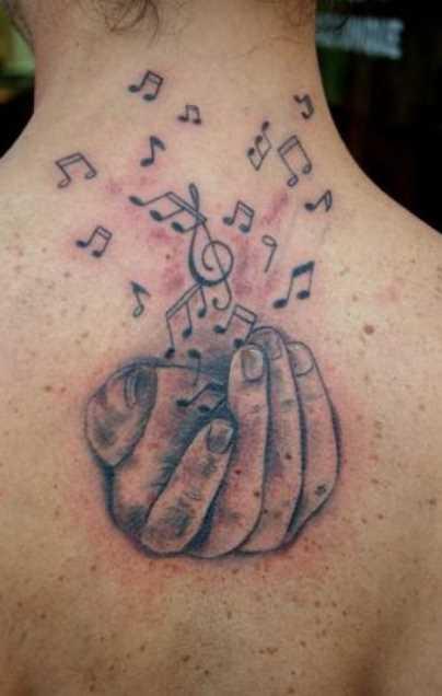 Tatuagem na espinha meninas - as notas da clave de sol na mão