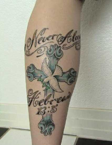 Tatuagem na perna da menina - a cruz, a pomba e a inscrição
