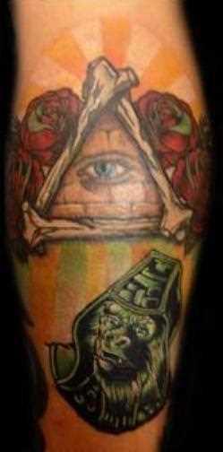 Tatuagem na perna da menina - a pirâmide com o olho e a rosa
