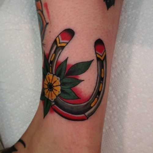 Tatuagem na perna da menina em forma de ferradura