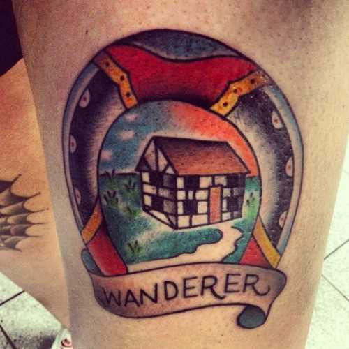 Tatuagem na perna da menina - ferradura, a casa e a inscrição