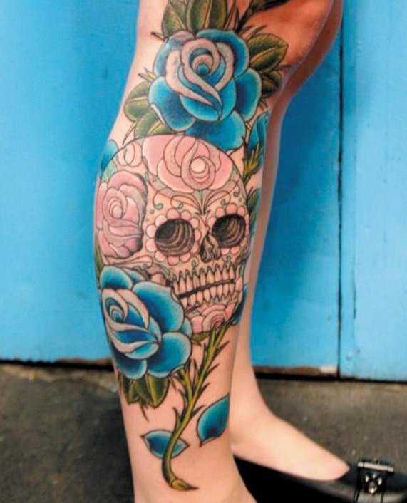 Tatuagem na perna da menina - rosas azuis e o crânio