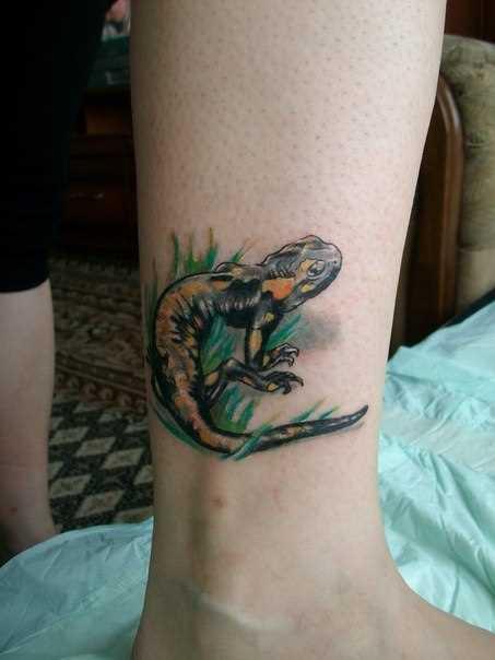 Tatuagem na perna da menina - salamandra na grama