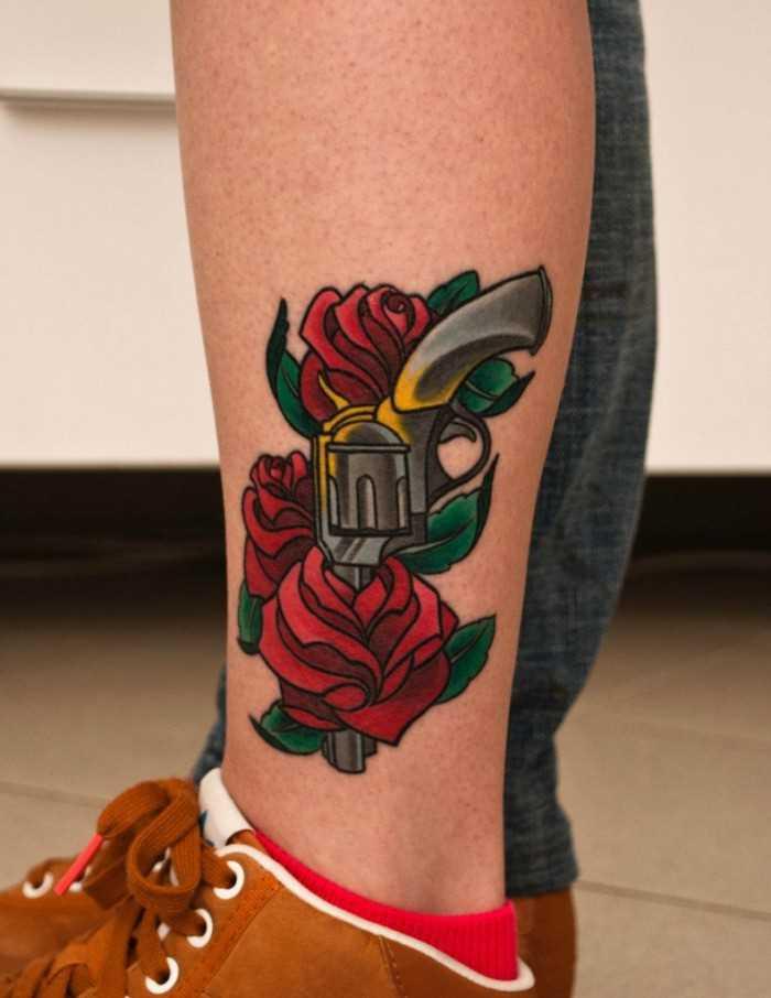 Tatuagem na perna da menina - uma pistola e rosas