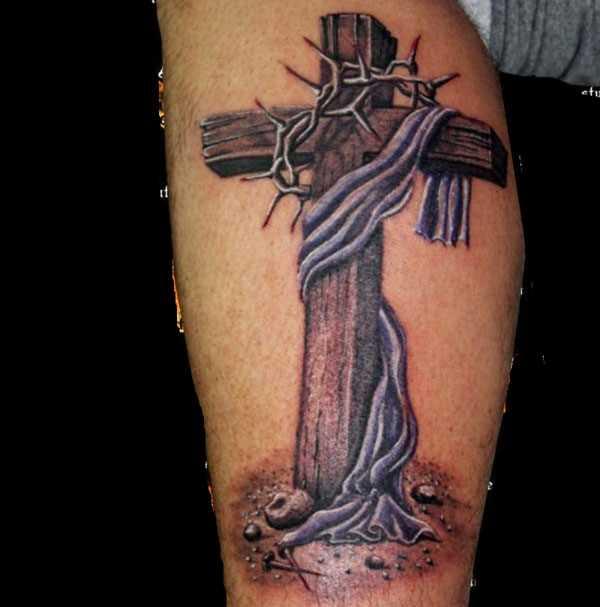 Tatuagem na perna de um cara - a cruz e a coroa de espinhos