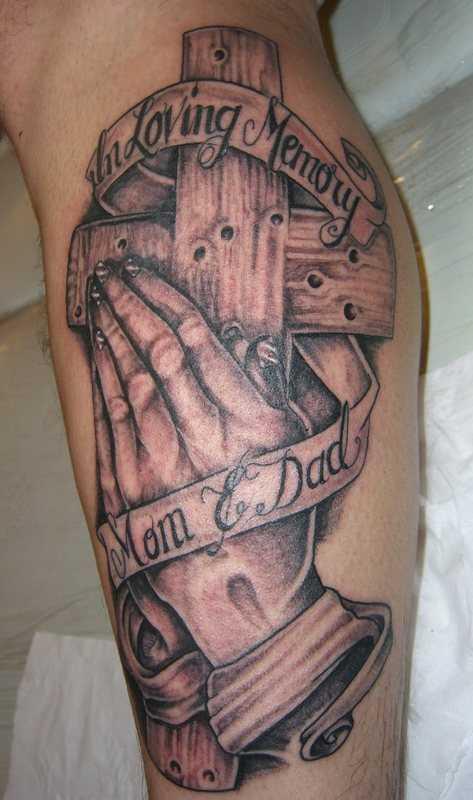 Tatuagem na perna de um cara - a cruz e a palma da mão, dobrado em oração