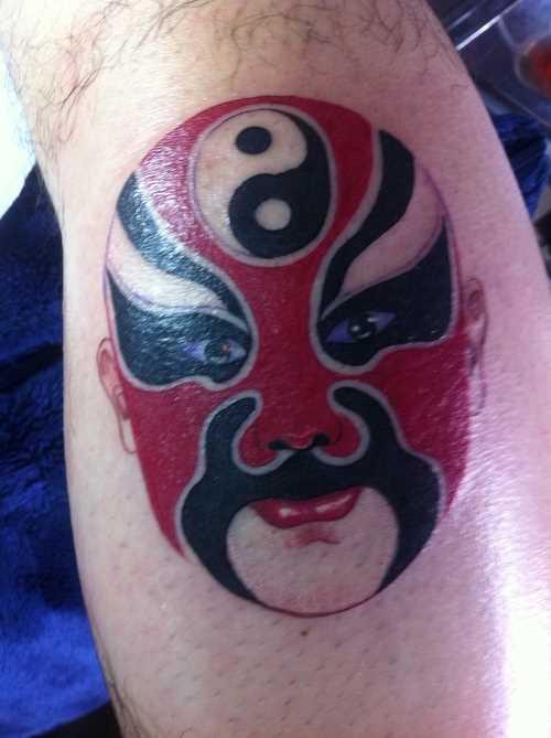 Tatuagem na perna de um cara - a máscara e sivol Yin-Yang