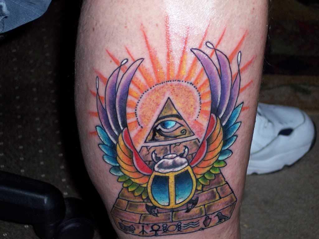 Tatuagem na perna de um cara - a pirâmide com o olho, um besouro de asas e o sol