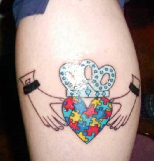 Tatuagem na perna de uma menina de quebra - cabeça em forma de coração com uma coroa