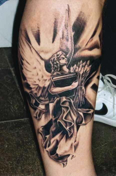 Tatuagem na perna do cara - de- anjo com um livro e penas