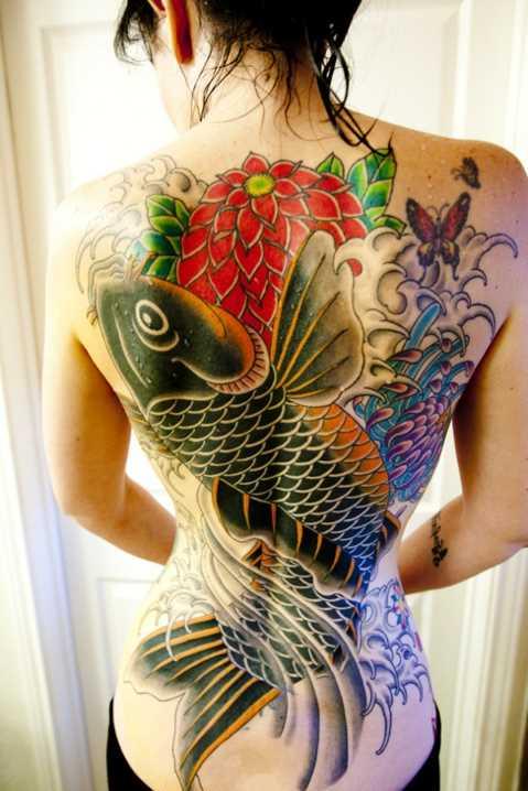 Tatuagem nas costas da menina - carpa, uma flor e uma borboleta