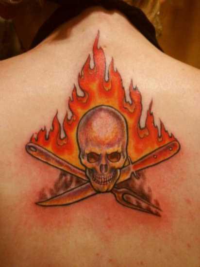 Tatuagem nas costas da menina - chama em forma de um crânio